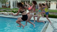 Group Of Teen Girls All Jump Into Deep End Of Swimming Pool At The Same Time Stock Footage