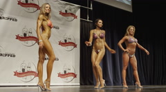 Low angle wide shot of bodybuilders posing on stage at competition / Draper, Stock Footage