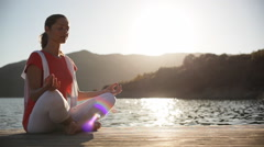 Pan shot of woman sitting by lakeside doing yoga Stock Footage