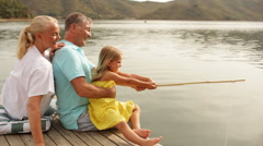 Mature couple with grandchild fishing by lakeside Stock Footage