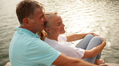 Mature couple sitting on jetty by lakeside Stock Footage