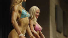 Low angle panning shot of bodybuilders posing on stage at competition / Draper, - stock footage