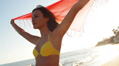 Young woman with shawl on beach Stock Footage