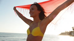 Young woman with shawl on beach - stock footage