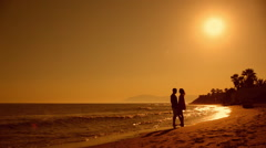 Young couple walking on beach in sunset Stock Footage