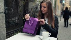 Happy young beautiful woman looking at just bought book in cafe HD Stock Footage