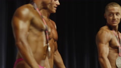 Low angle close up of winning bodybuilders posing on stage after competition / Stock Footage