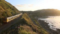 Metro commuter train and traffic at sunset on scenic highway along Kapiti coast Stock Footage