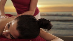 dolly shot of young woman having massage, sunset and beach background - stock footage
