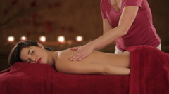 Young woman having massage, candlelit background Stock Footage
