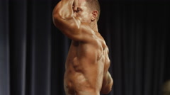 Low angle close up of bodybuilder posing on stage at competition / Draper, Utah, - stock footage