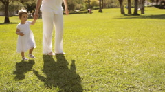 pan shot of mother and baby walking in park - stock footage