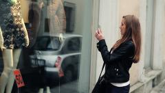 Woman taking photo of clothes in shop window with smartphone HD Stock Footage