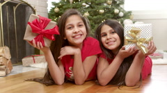 Sisters lay on the floor in front of the christmas tree and hold up presents Stock Footage