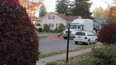 City Truck removing leaves in front a neighborhood home Stock Footage