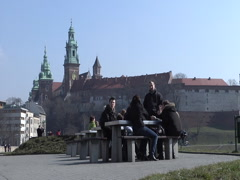 People seated/talking with Wawel Castle Stock Footage