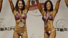 Stock Video Footage of Panning shot of winning bodybuilders posing on stage at competition / Draper,