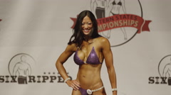 Panning shot of winning bodybuilder holding trophy on stage at competition / Stock Footage