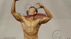 Panning shot of bodybuilder posing on stage at competition / Draper, Utah, Stock Footage