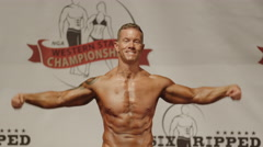 Bodybuilder posing on stage at competition / Draper, Utah, United States - stock footage