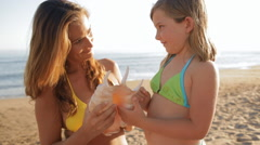 Little girl and mother with seashell on beach Stock Footage