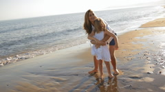 Mother spinning daughter around on beach Stock Footage