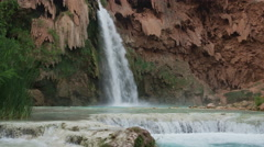 Wide slow motion panning shot of waterfall in rocky landscape / Havasupai, Stock Footage