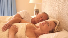 Dolly shot of senior couple asleep in bed Stock Footage