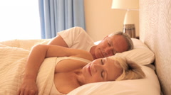 dolly shot of senior couple asleep in bed - stock footage