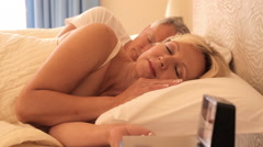 dolly shot of senior couple asleep in bed woman waking and turning off alarm - stock footage