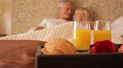 Dolly shot of senior couple sitting in bed with breakfast in foreground Stock Footage