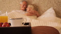dolly shot of senior couple sitting in bed with breakfast in foreground - stock footage