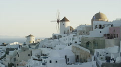 Wide slow motion shot of rooftops in hillside cityscape / Oia, Santorini, Greece Stock Footage