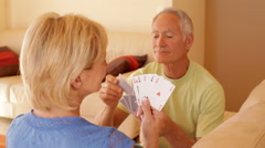 Dolly shot of senior couple relaxing on sofa playing cards Stock Footage