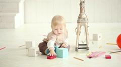 little boy playing on the floor in a bright room - dolly shot - stock footage