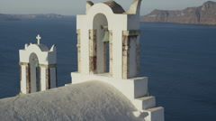 Medium slow motion shot of church bell and arch overlooking ocean / Oia, Stock Footage