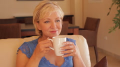 dolly shot of senior woman relaxing on sofa with drink - stock footage