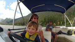 Slow motion shot of child driving a boat with family on mountain lake Stock Footage