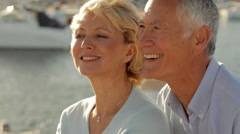 Stock Video Footage of head and shoulders shot of senior couple sitting together by marina in sunset