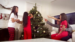 A family decorates a christmas tree together in the living room - stock footage