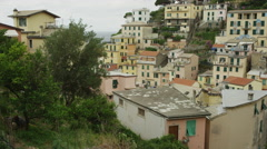 Slow motion panning shot of village built on hillside / Riomaggiore, Cinque Stock Footage