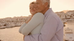 senior couple hugging by marina in sunset - stock footage
