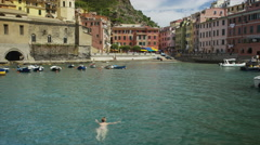 Slow motion panning shot of woman swimming in village harbor / Vernazza, Cinque Stock Footage