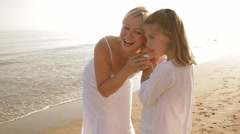 grandmother and granddaughter on beach with large shell - stock footage