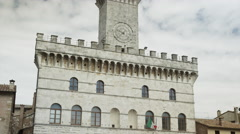 Low angle panning shot of church and clock tower / Val d'Orcia, Tuscany, Italy Stock Footage
