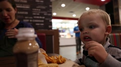 Mother and toddler eating fast food Stock Footage