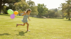 Young girl running with balloons in park Stock Footage