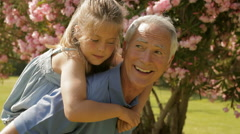 Grandfather and granddaughter playing in park Stock Footage