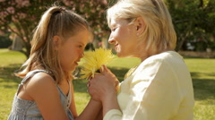 grandmother and granddaughter playing with flower in park - stock footage