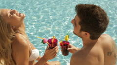 young couple sitting by side of pool with drinks - stock footage